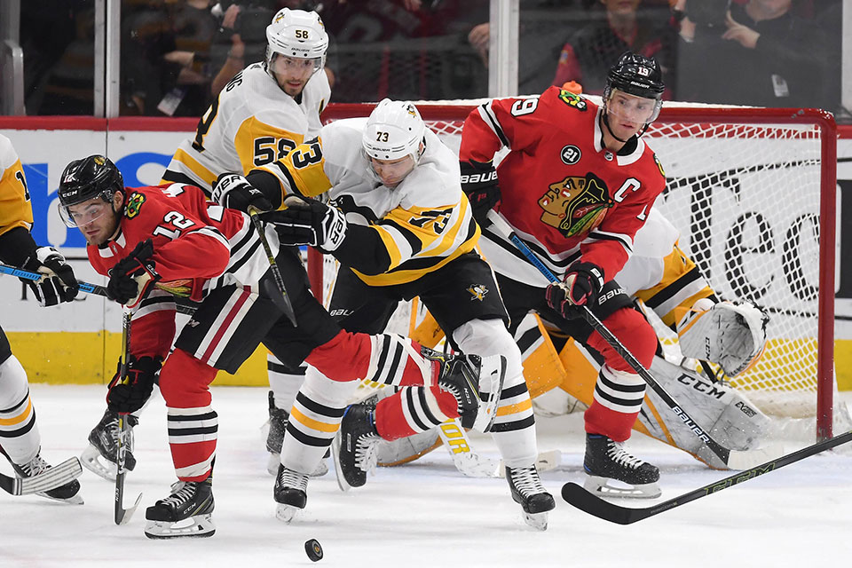 Pittsburghs Jack Johnson (Mitte) gegen Chicagos Alex DeBrincat.