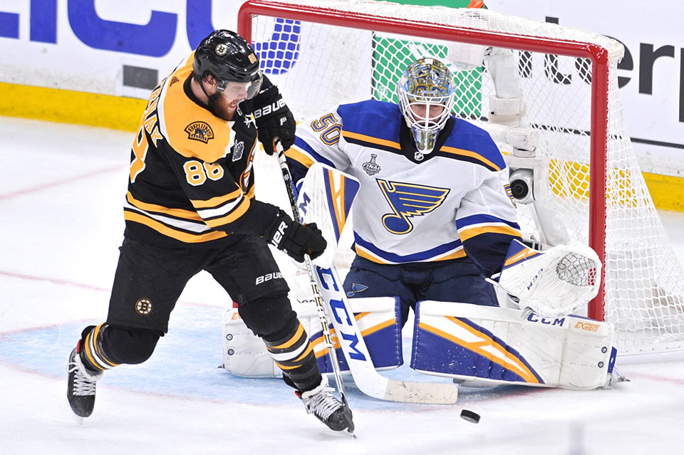 Bostons David Pastrnak vor Blues-Torhüter Jordan Binnington.